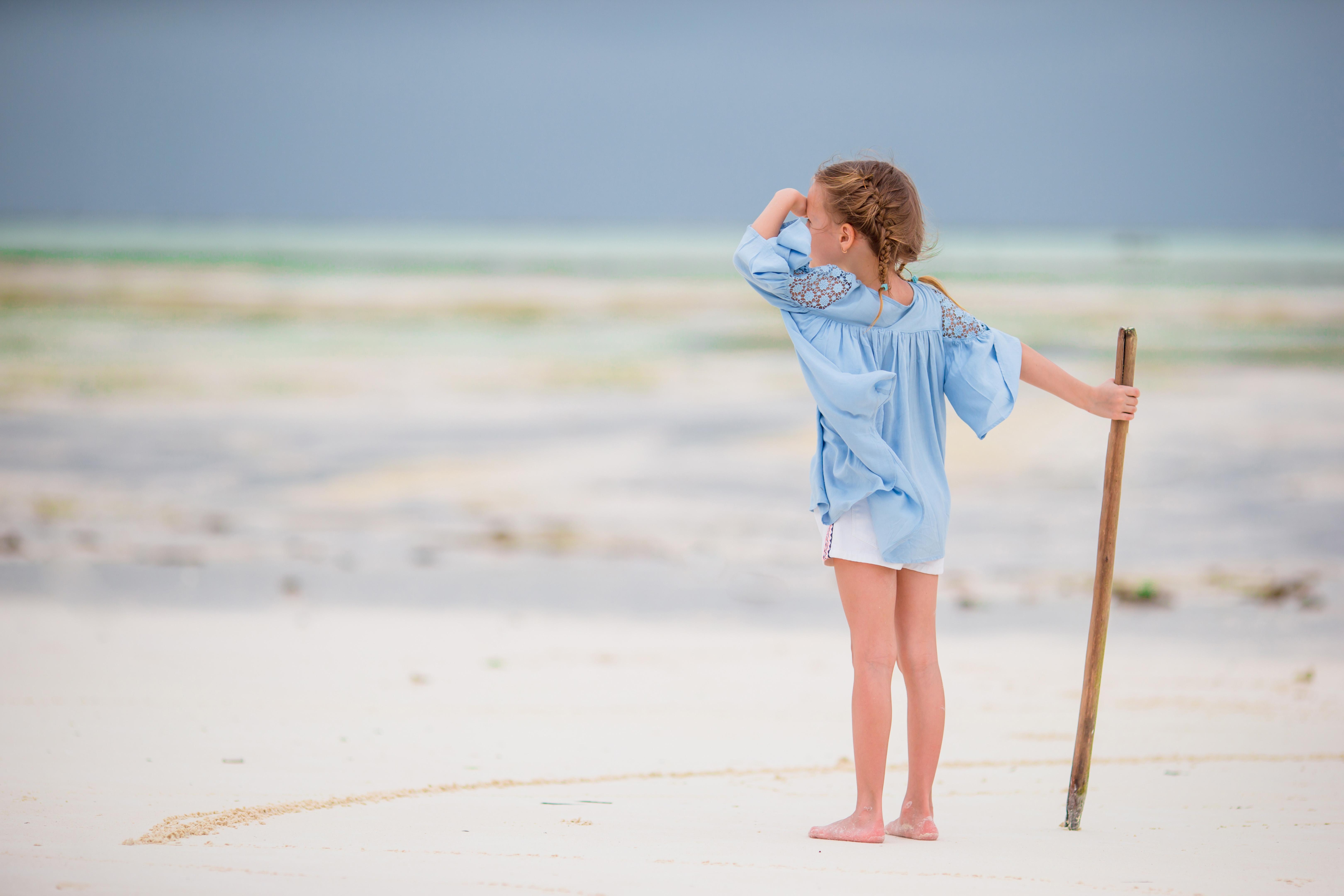 Adorable little girl on beach vacation having fun